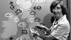 A black and white shot of a woman standing in front of an old weather chart with classic weather symbols of clouds and suns.