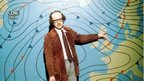A man wearing glasses and and a long brown jacket stands in front of a weather chart.