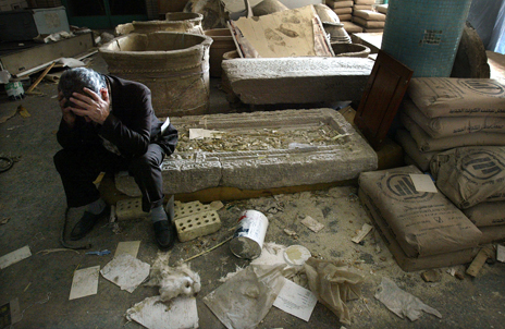 An Iraqi Museum official sits amid looted wreckage just after the 2003 invasion