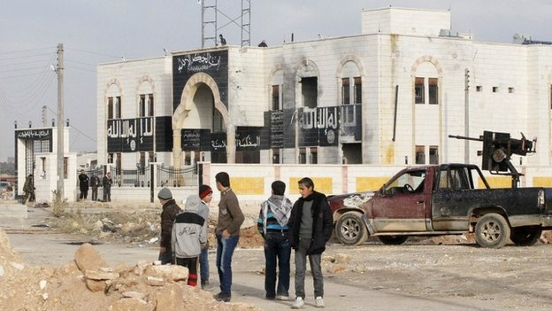 People stand outside a former Islamist State in Iraq and the Levant (ISIS) in Dana, Idlib province (9 January 2014)