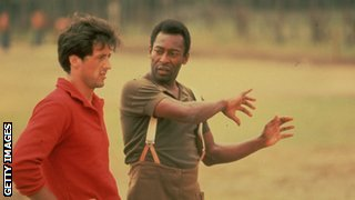 Pele attempts to teach Stallone some goalkeeping skills during the filming of 'Escape to Victory'