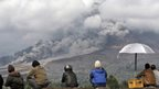 Villagers watch Mount Sinabung release pyroclastic flows in Tiga Kicat, North Sumatra, Indonesia, Friday, Jan. 10, 2014.