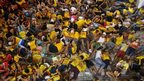 Barefoot devotees sleep on a pavement before the arrival of the Black Nazarene at the Quiapo Church in Manila late on January 9, 2014.