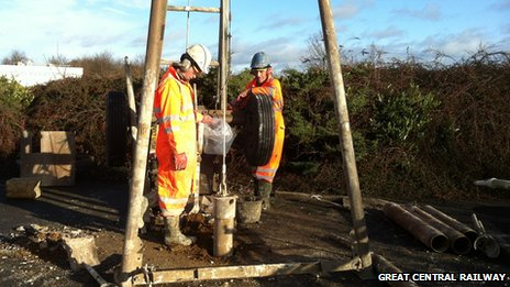 Workmen drilling boreholes to test the ground conditions ready for a bridge