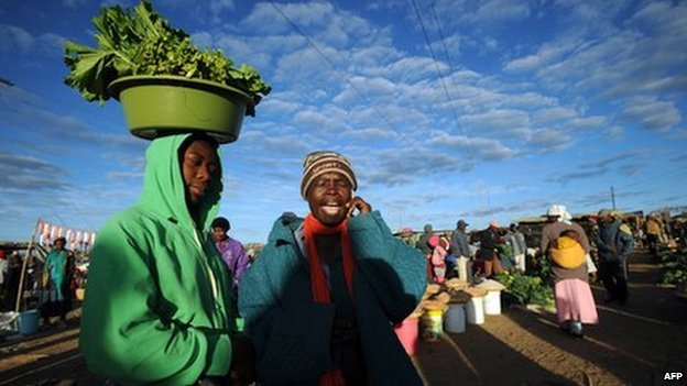 Zimbabwean women shop for vegetables in Jambanja market in Seke, south of Harare, on 2 August 2013