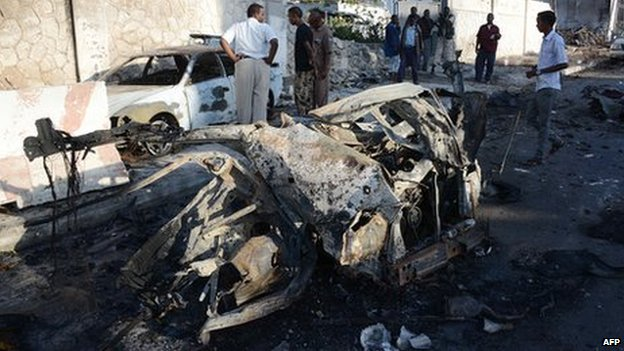 Somali residents look at the wreckage of two cars on 2 January 2014 in Mogadishu