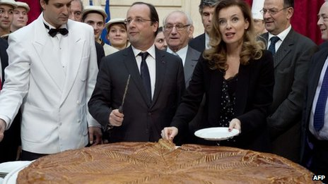 French President Francois Hollande (C) and his partner Valerie Trierweiler (3rd R) cutting slices of a traditional epiphany cake at the Elysee palace