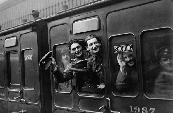 Soldiers wave from the window of a train