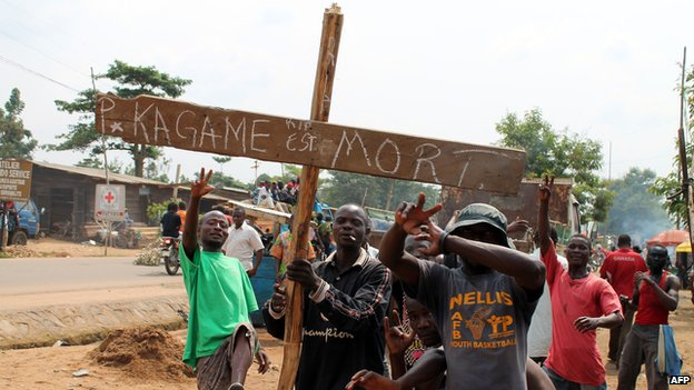 """Residents in Goma hold a cross saying """"Kagame is dead"""" on hearing false rumours that the Rwandan president had died"""