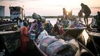 People arriving in boats in Minkammen, South Sudan, at sunrise - Thursday 9 January 2014