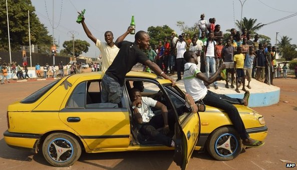 People celebrate in Bangui after the announcement of the resignation of President Djotodia