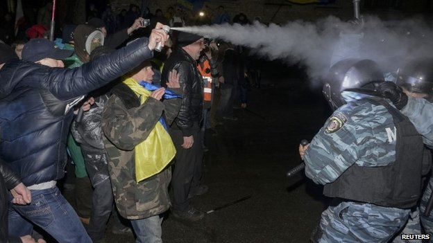 Opposition activist uses spray against riot police during a rally near a court in Kiev (10 January 2014)