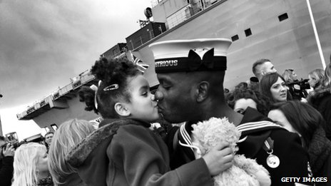 Crewmember Yuri Teller kisses his daughter as he returns home on HMS Illustrious