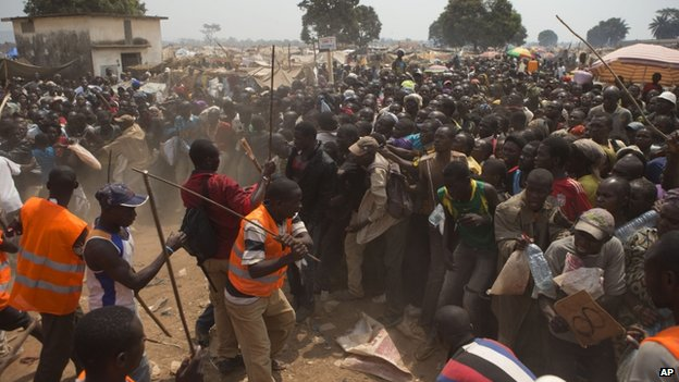 Security volunteers use sticks to fend off the crowd trying to enter a food and supplies distribution point, at a makeshift camp housing an estimated 100,000 displaced people, at Mpoko Airport, in Bangui