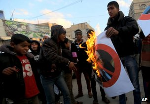 Palestinians burn a poster of Ariel Sharon in Khan Younis, Gaza Strip, 11 January
