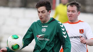 Owain Beggs of Dundela shields the ball from Carrick's Ryan McCann