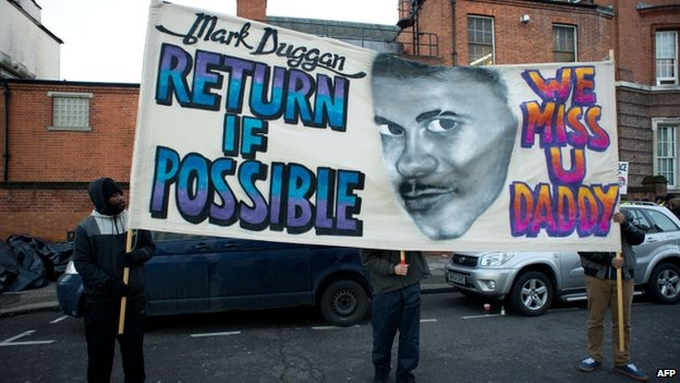 Three people hold a banner depicting Mark Duggan's face