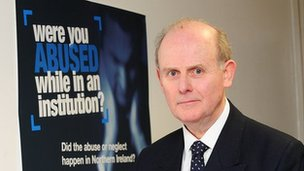 Sir Anthony Hart poses in front of the inquiry's appeal poster
