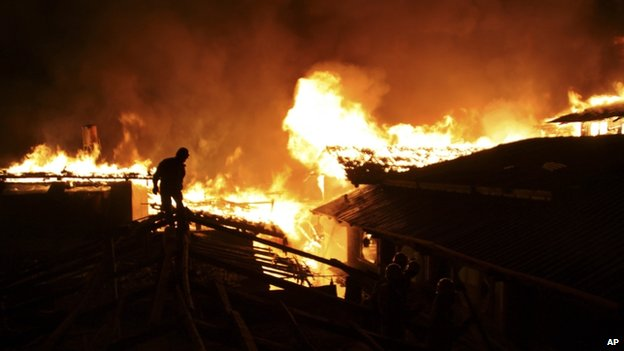 A firefighter works on a roof of a wooden building while a fire ravages ancient Dukezong town