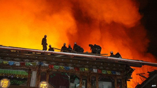 Firefighters work on a roof of a wooden building while a fire ravages ancient Dukezong town