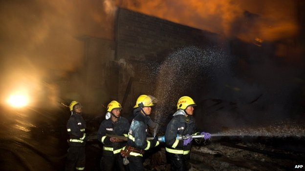 Firefighters put out a fire in the ancient Tibetan village of Dukezong in Shangri-La county