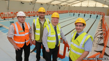 Contractors and councillors gather around the pool