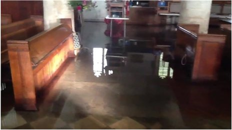 Floodwater in between pews in the Parish Church of St Mary the Virgin in Charminster, Dorset
