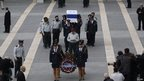 Members of the Knesset guard carry the flag draped coffin of former Israeli prime minister Ariel Sharon