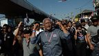 Thai protest leader Suthep Thaugsuban (C) sings a song along with anti-government protesters as they march through the streets of Bangkok in a move to