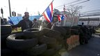 Anti-government protesters wave national flags as they block intersection during rally in Bangkok on 13 January 2014