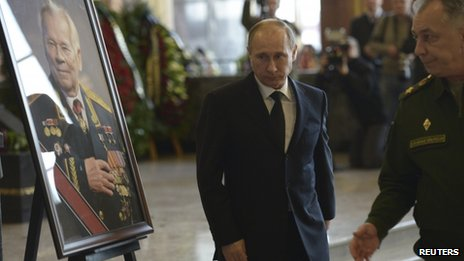 Russian President Vladimir Putin walks past a portrait of Mikhail Kalashnikov during a memorial ceremony outside Moscow, December 27, 2013