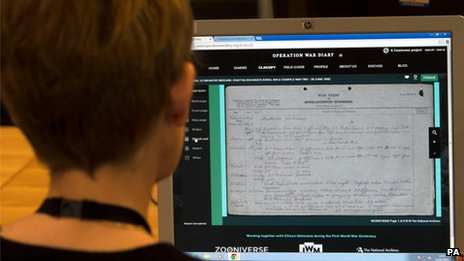 Woman looks at World War One diary on computer screen at the National Archives