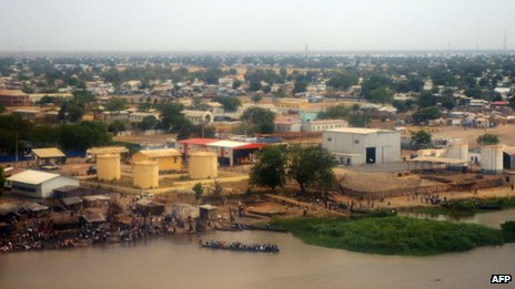 People gather on the banks of the White Nile in Malakal as a boat moves along the river. Photo: 12 January 2014