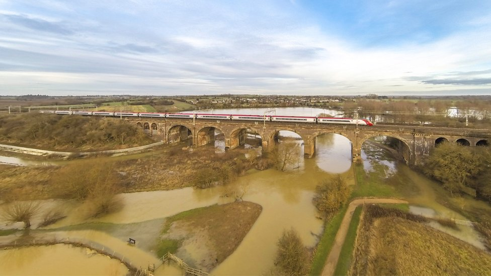 A Virgin Train travels over Wolverton Viaduct in Buckinghamshire