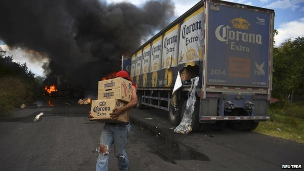 A looter carries boxes of beer as Corona truck burns in a road block allegedly set up by followers of the Knights Templar cartel in Tierra Caliente on 10 January, 2014