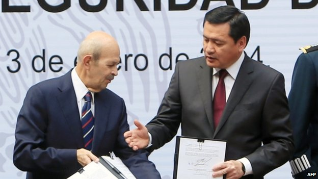 Mexican Interior Secretary Miguel Angel Osorio Chong (right) extends his hand to Michoacan state Governor Fausto Vallejo