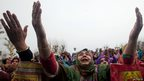 Kashmiri Muslim devotees raise their hands in prayer as a head priest displays a relic of Prophet Muhammad at the Hazratbal shrine on the anniversary of the birth of Prophet Muhammad, in Srinagar, Indian-administered Kashmir on 14 January 2014
