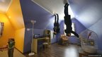 A picture rotated 180 degrees shows visitors walking on the ceiling of an 'upside-down house' attraction at the VVTs the All-Russia Exhibition Centre in Moscow, on 14 January 2014