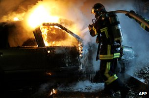Policeman work to put out a burning car set alight during unrest in the suburbs of Strasbourg in November 2005