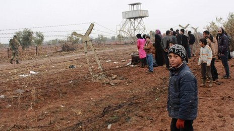 Syrian refugees wait to cross border into Turkey. 13 Jan 2014