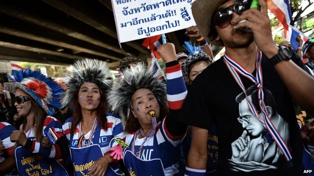 A Thai anti-government protester blows a horn as he takes part in a march through downtown Bangkok on 15 January 2014