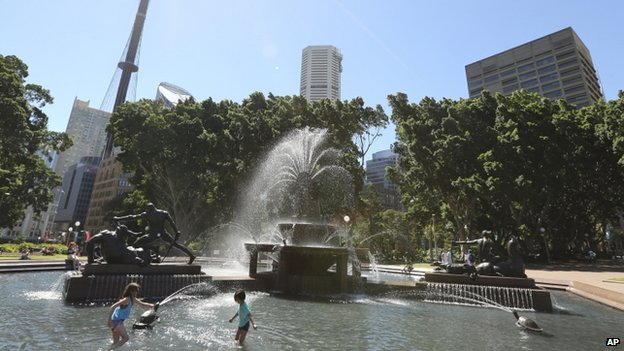 Children dip in a fountain to cool off in the hot weather in the central business district of Sydney, Australia, 15 January 2014