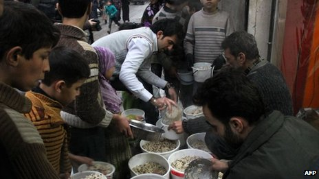 Syrian youths gather to receive aid food in the northern Syrian city of Aleppo