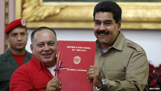Venezuelan President Nicolas Maduro (right) receives from National Assembly President Diosdado Cabello a document approving a law which grants him with decree powers in Caracas on 19 November, 2013