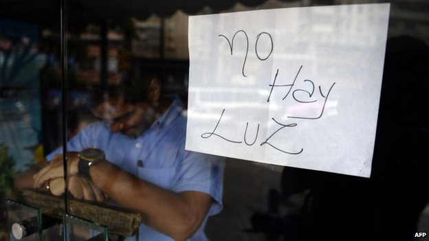 "An employee of a business closed during a blackout stands behind the door with a notice reading ""There's no electricity"" in Caracas on 3 September, 2013"