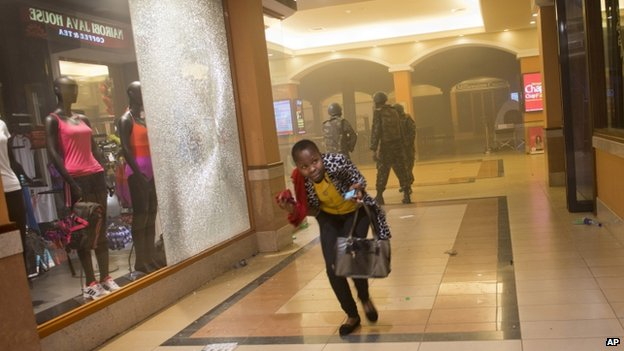A woman who had been hiding during the gun battle runs for cover after armed police enter the Westgate mall in Nairobi, Kenya -21 September 2013