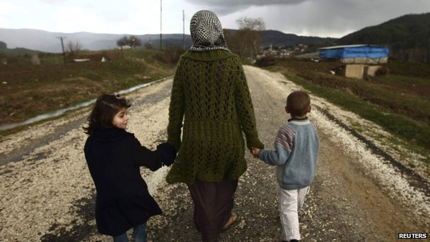 Syrian woman walking with two children