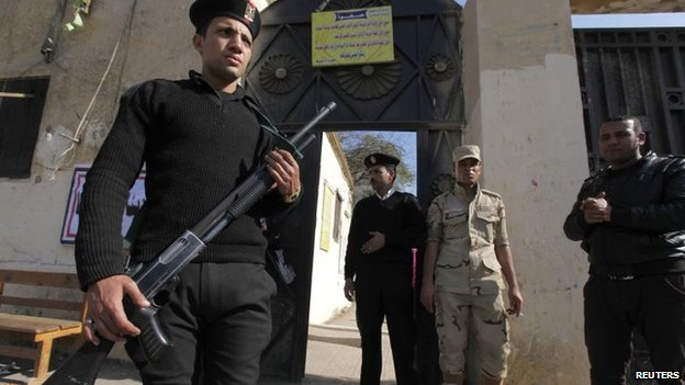 Egyptian police and a soldier stand guard outside a polling station
