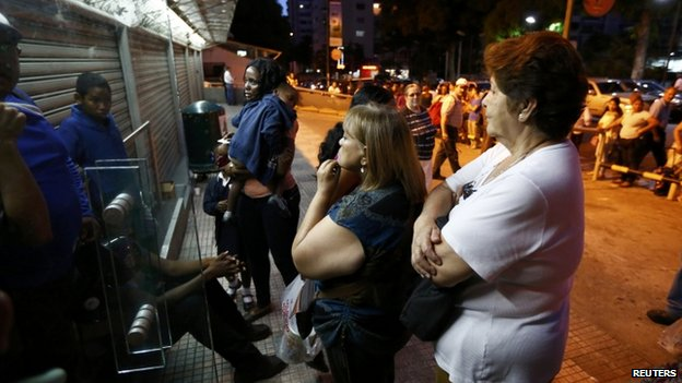 People wait to buy products outside a supermarket in Caracas on 15 November, 2013