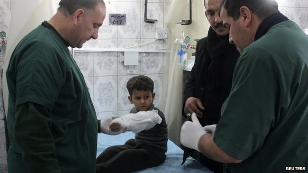 Medics treat a boy injured in the bombing outside Baquba (15 January 2014)